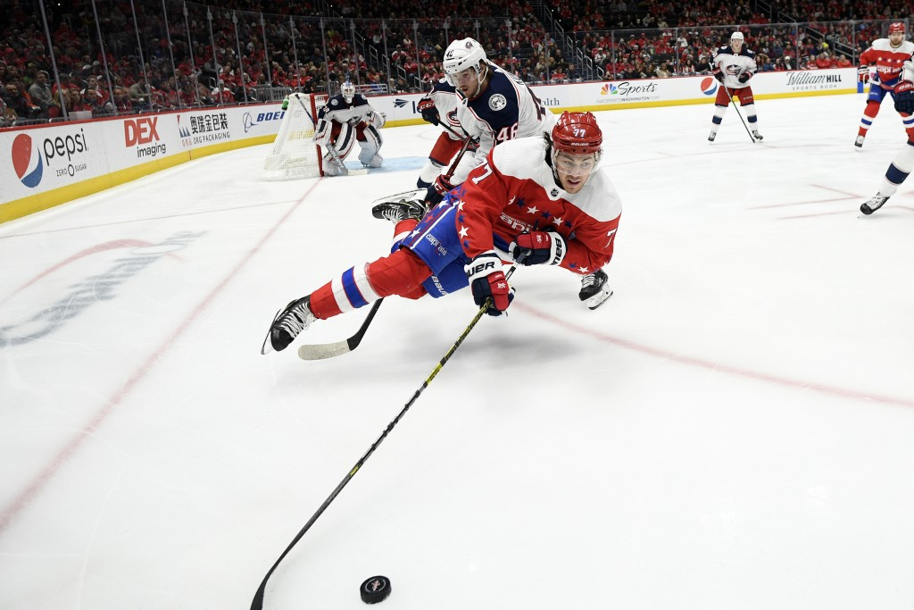 Washington Capitals right wing T.J. Oshie (77) is tripped by Columbus Blue Jackets defenseman Dean Kukan, back, during the second period of an NHL hoc...