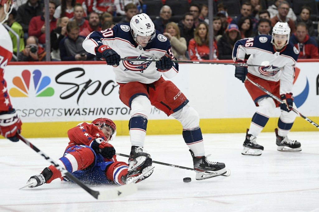 Washington Capitals center Lars Eller, bottom, and Columbus Blue Jackets left wing Eric Robinson (50) compete for the puck during the first period of ...