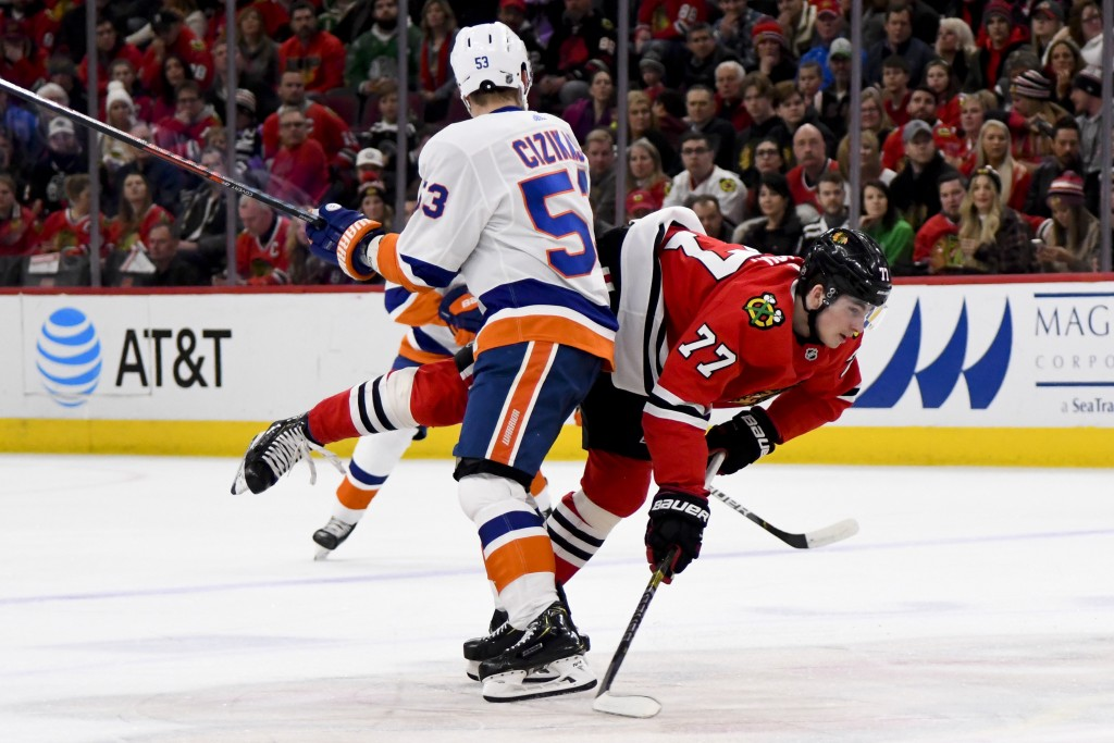 New York Islanders center Casey Cizikas (53) and Chicago Blackhawks center Kirby Dach (77) collide during the first period of an NHL hockey game Frida...