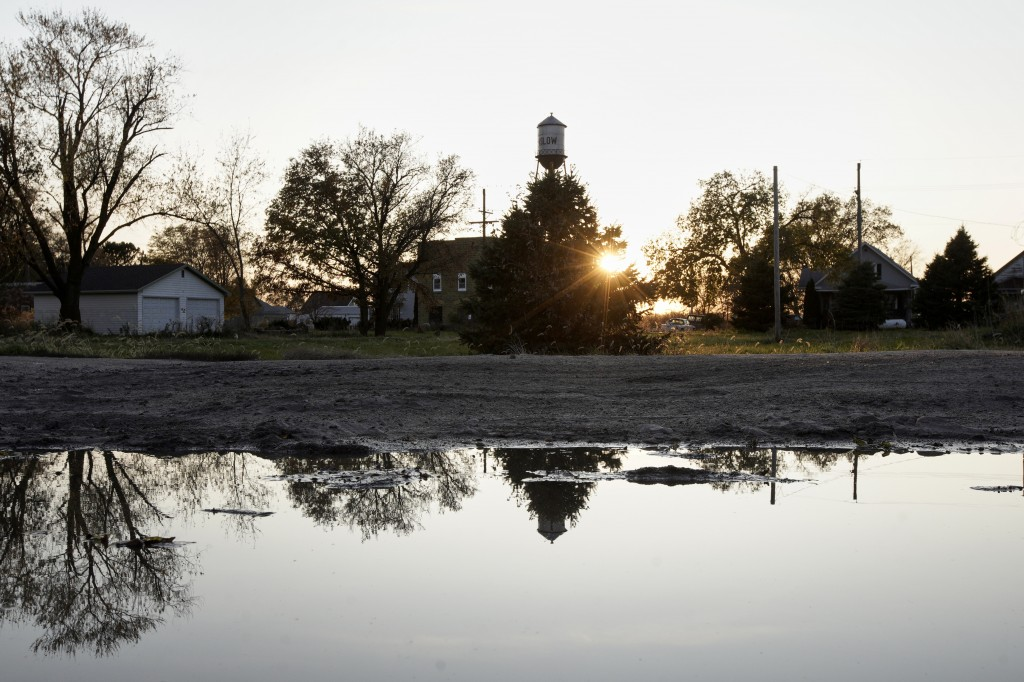 In this Oct. 24, 2019 photo, the setting sun and homes are reflected in a puddle, in Winslow, Neb. It took only minutes for swift-moving floods from t...