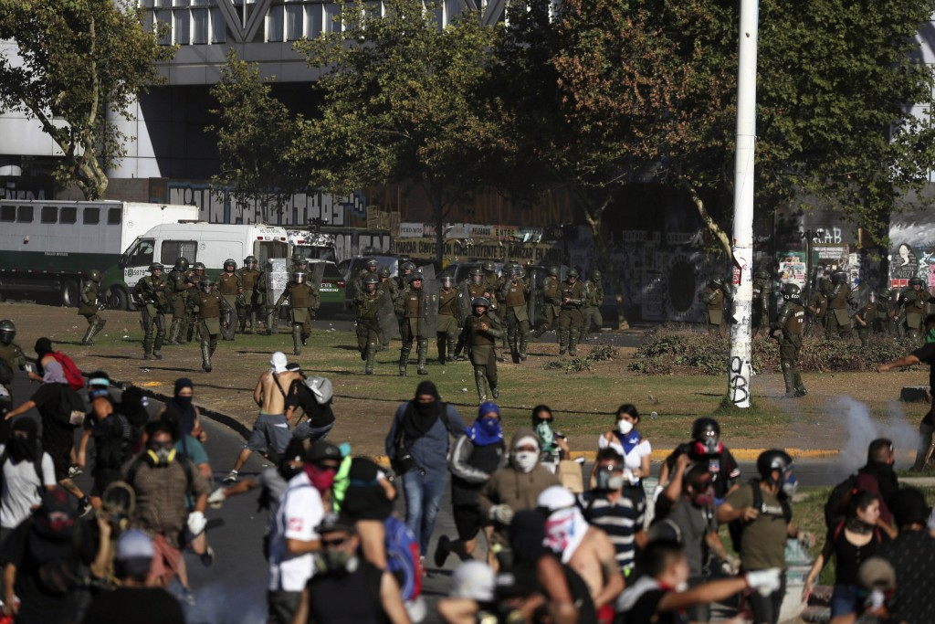Chilean policemen run toward anti-government demonstrators during a protest in Santiago, Chile, Friday, Dec. 27, 2019. Chile has been roiled by contin...
