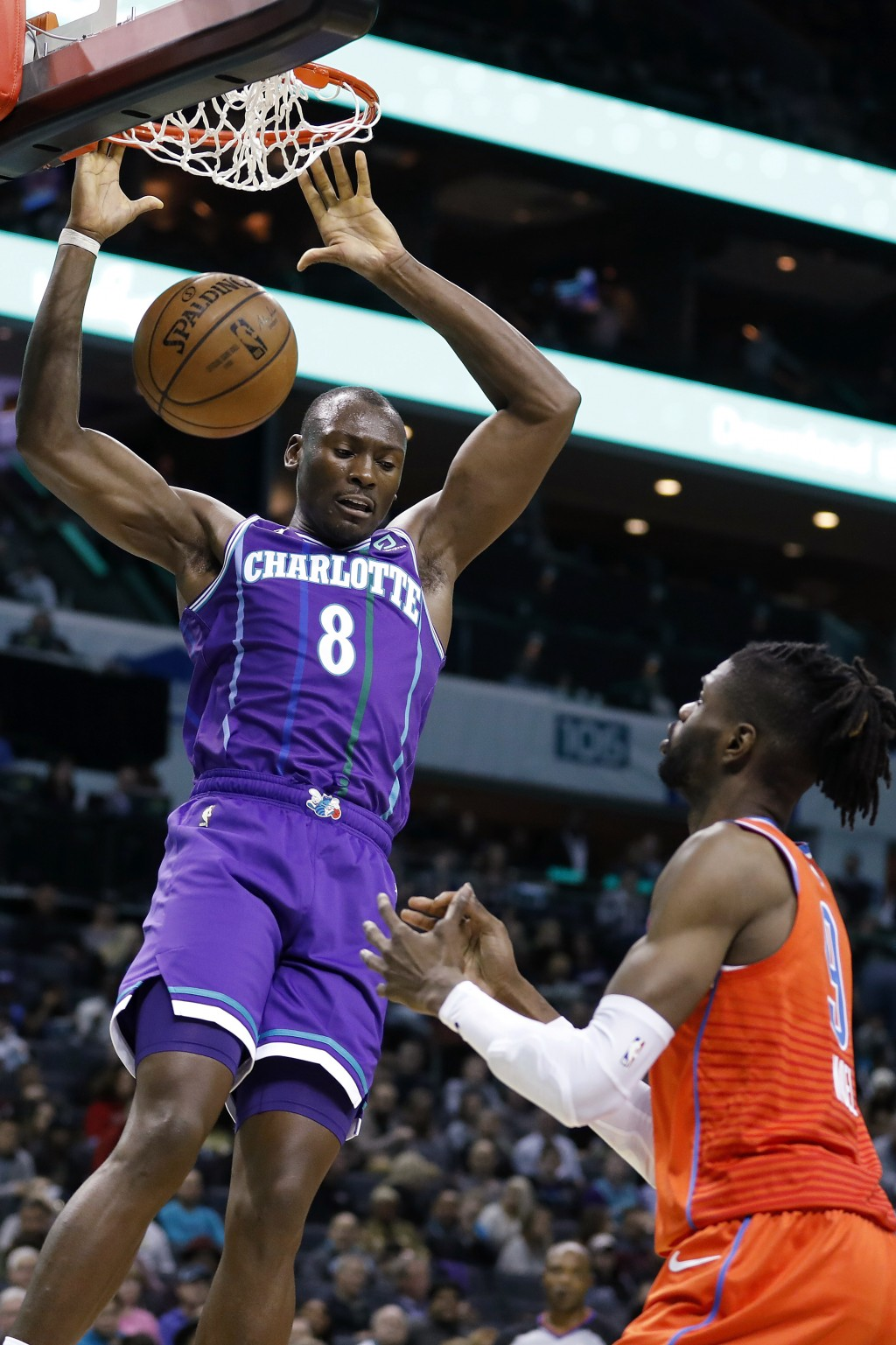 Charlotte Hornets' Bismack Biyombo (8) dunks as Oklahoma City Thunder's Nerlens Noel (9) watches during the first half of an NBA basketball game in Ch...