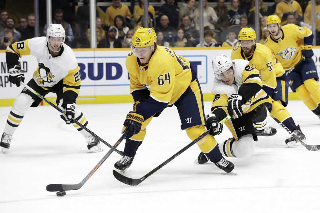 Nashville Predators center Mikael Granlund (64), of Finland, moves the puck ahead of Pittsburgh Penguins defenseman John Marino (6) during the second ...