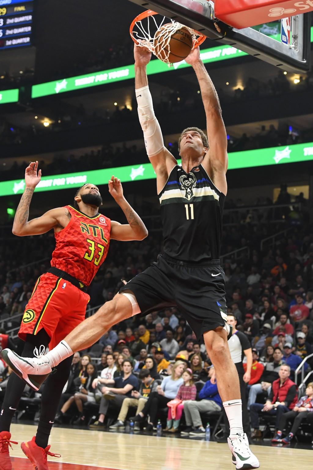Milwaukee Bucks center Brook Lopez (11) dunks against Atlanta Hawks guard Allen Crabbe during the first half of an NBA basketball game Friday, Dec. 27...