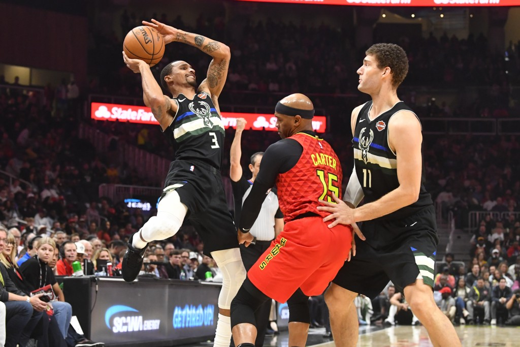 Milwaukee Bucks guard George Hill (3) tries to shoot as center Brook Lopez (11) sets a pick on Atlanta Hawks guard Vince Carter during the first half ...