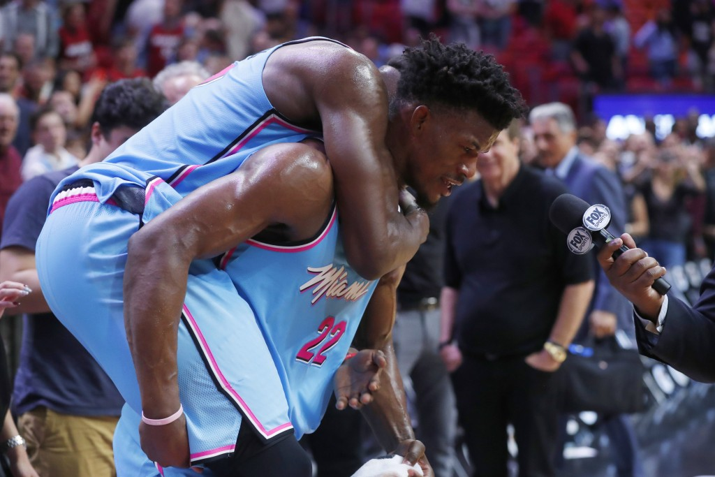 Miami Heat center Bam Adebayo jumps onto the back of forward Jimmy Butler as Butler is interviewed after the team's NBA basketball game against the In...