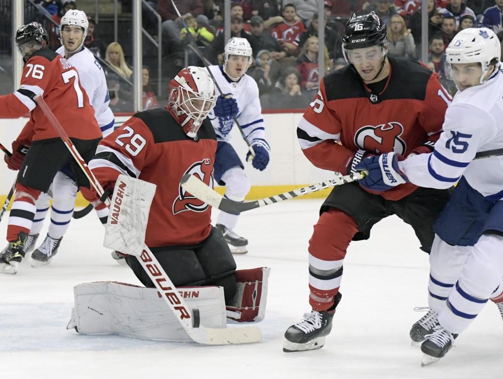 New Jersey Devils goaltender Mackenzie Blackwood (29) deflects the puck as Devils center Kevin Rooney (16) and Toronto Maple Leafs center Alexander Ke...