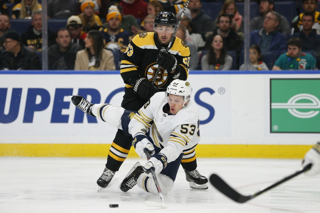 Buffalo Sabres forward Jeff Skinner (53) is checked by Boston Bruins forward Brad Marchand (63) during the second period of an NHL hockey game Friday,...