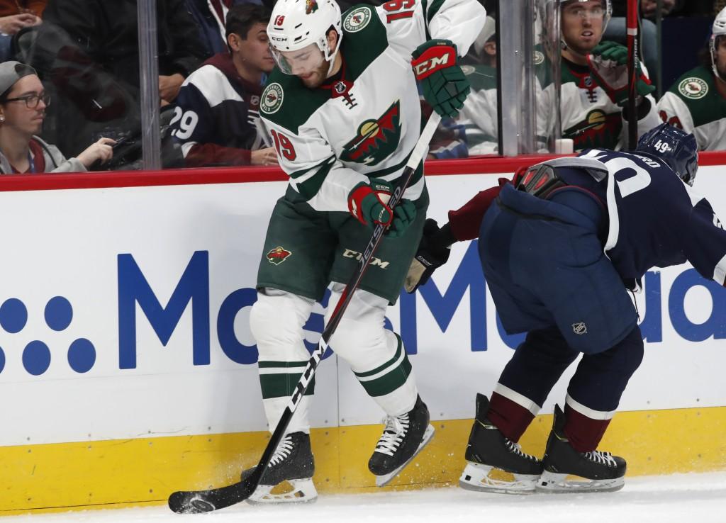 Minnesota Wild center Luke Kunin, left, slips past Colorado Avalanche defenseman Samuel Girard in the second period of an NHL hockey game Friday, Dec....