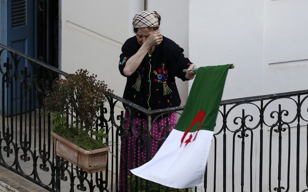 A woman wipes her face while carrying a national flag as protesters take to the streets in the capital Algiers to reject the presidential elections an...