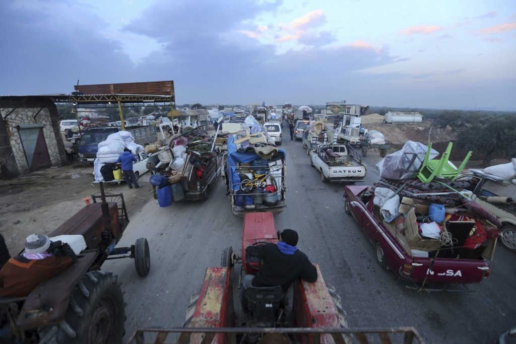 Truckloads of civilians flee a Syrian military offensive in Idlib province on the main road near Hazano, Syria, Tuesday, Dec. 24, 2019. Syrian forces ...