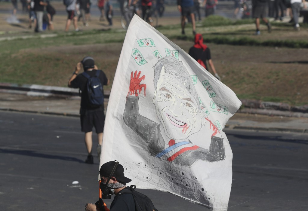 A Chilean anti-government demonstrator waves a flag with the image of Chile's President Sebatian Pinera during a protest in Santiago, Chile, Friday, D...
