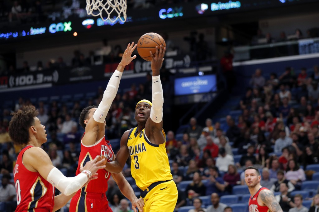 Indiana Pacers guard Aaron Holiday (3) goes to the basket against New Orleans Pelicans guard Josh Hart during the first half of an NBA basketball game...