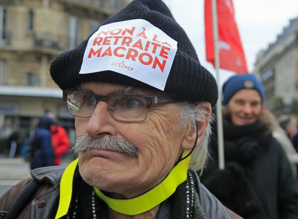 "A demonstrators wears a sticker on his hat that reads, ""no to Macron's pension reform during a protest in Paris, Saturday, Dec. 28, 2019. Thousands of..."