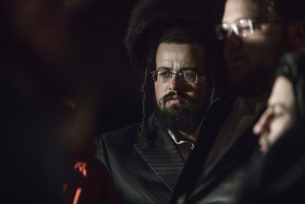 Orthodox Jewish gather on a street in Monsey, N.Y., Sunday, Dec. 29, 2019, following a stabbing late Saturday during a Hanukkah celebration. A man att...