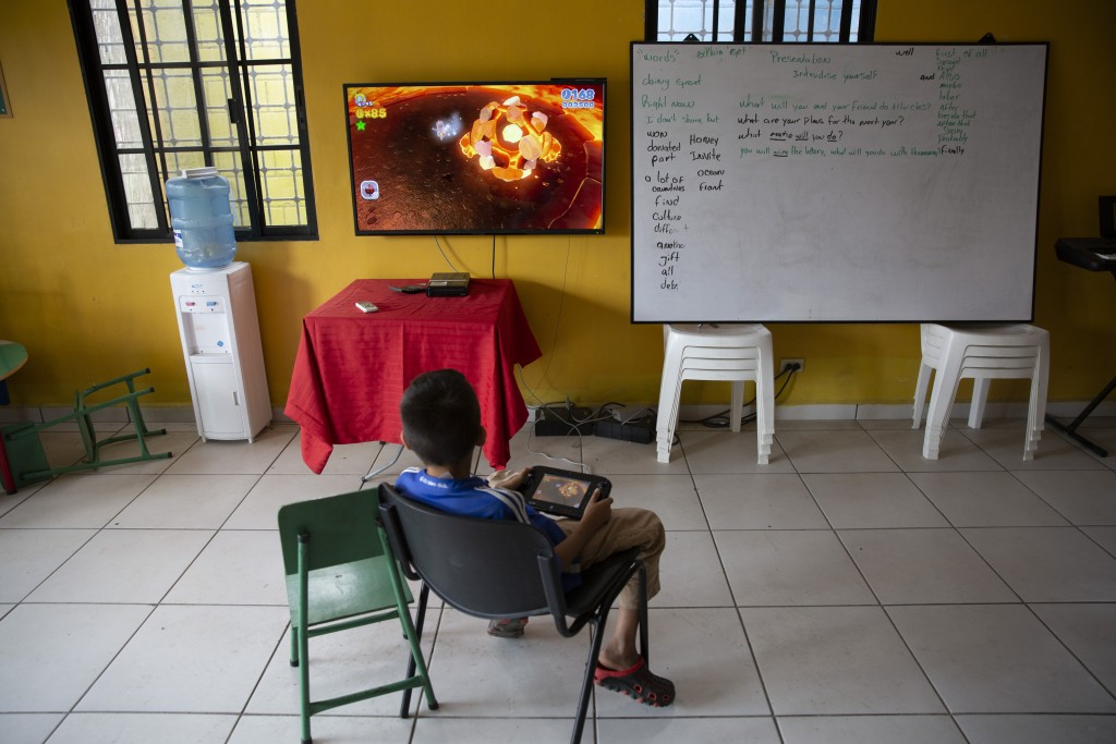 A boy plays video games inside a help center for young people living in dangerous zones, in the Rivera Hernandez neighborhood of San Pedro Sula, Hondu...