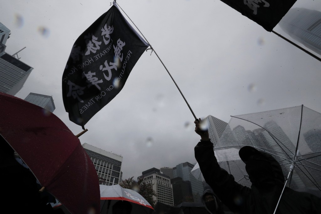 """A protester waves a flag with the words """"Liberate Hong Kong, Revolution of Our Times"""" in Hong Kong on Sunday, Dec. 29, 2019. Protests that began in Ju..."""