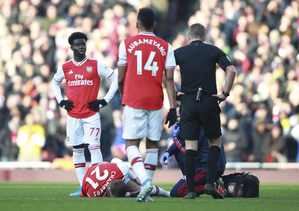 Arsenal's Calum Chambers lies injured on the pitch during the English Premier League soccer match between Arsenal and Chelsea, at the Emirates Stadium...