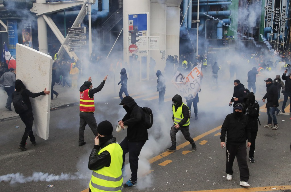 Demonstrators run away from teargas fired by police during a protest against pension reform plans in Paris, Saturday, Dec. 28, 2019. Thousands of prot...