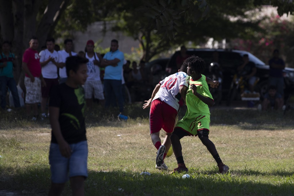 Players from a taxi drivers' team, center left, and a gang members' team vie for the soccer ball during a game in the Rivera Hernandez neighborhood of...