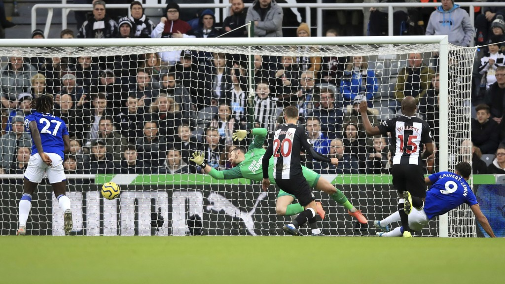 Everton's Dominic Calvert-Lewin, right, scores against Newcastle United during the English Premier League soccer match at St James' Park, Newcastle, E...