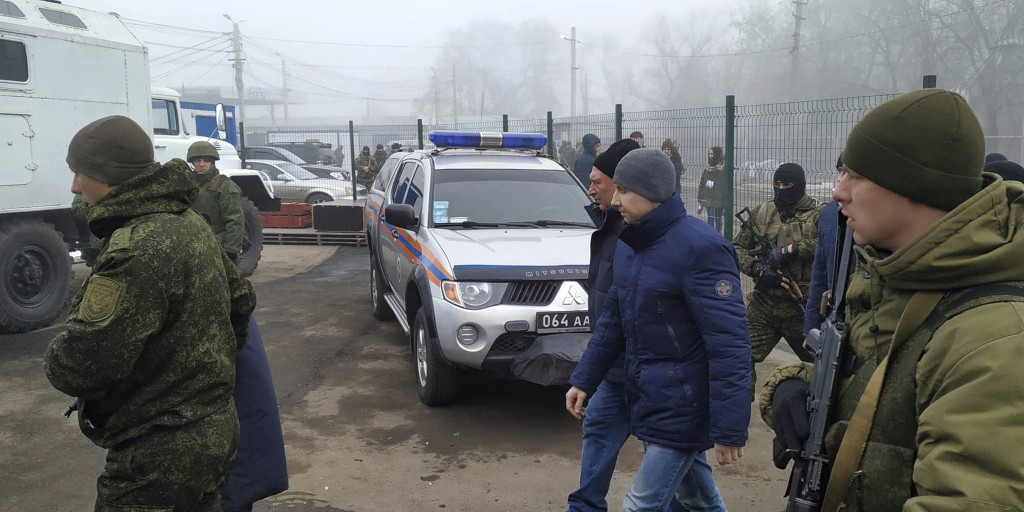Ukrainian war prisoners escorted by Russia-backed separatist soldiers walk to be exchanged near the checkpoint Horlivka, eastern Ukraine, Sunday, Dec....