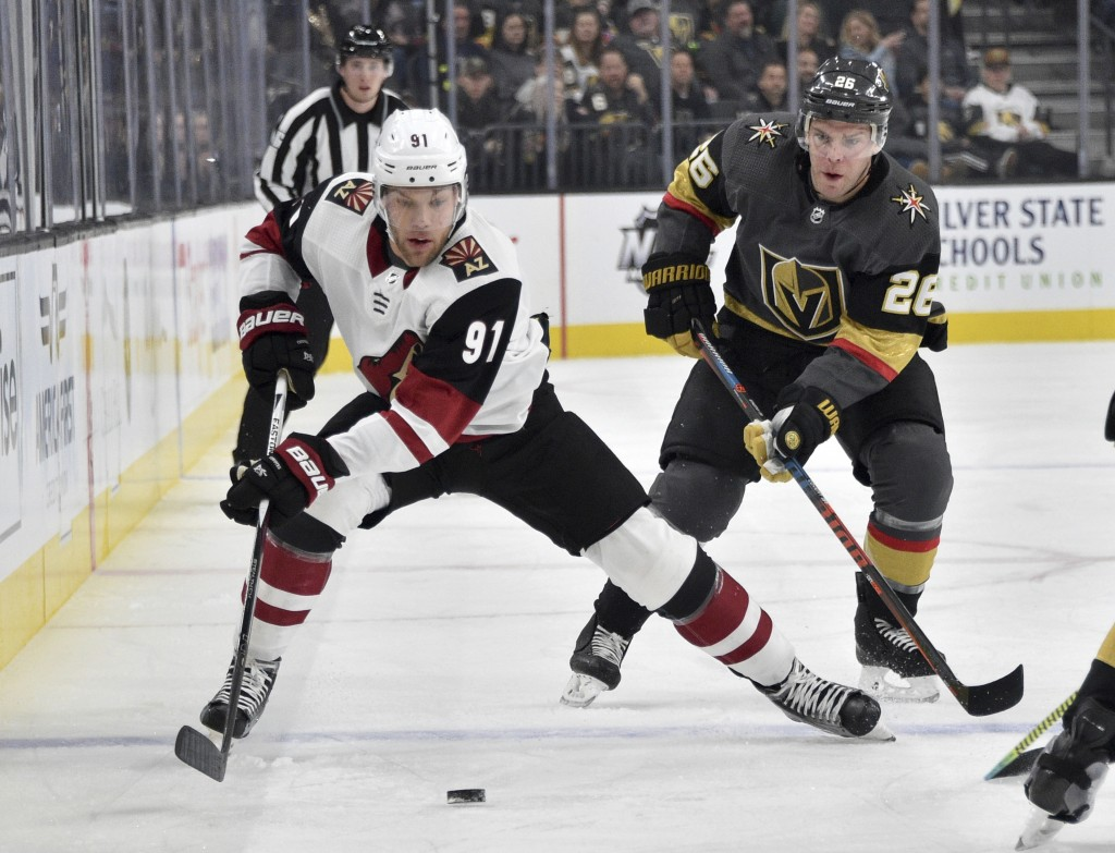 Arizona Coyotes left wing Taylor Hall (91) skates with the puck against Vegas Golden Knights center Paul Stastny during the first period of an NHL hoc...
