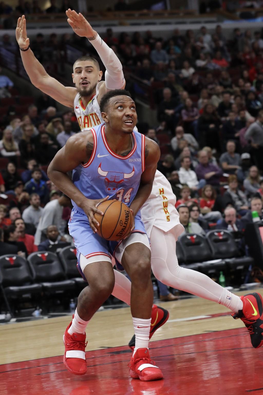 Chicago Bulls center Wendell Carter Jr., bottom, looks to the basket against Atlanta Hawks center Alex Len during the second half of an NBA basketball...