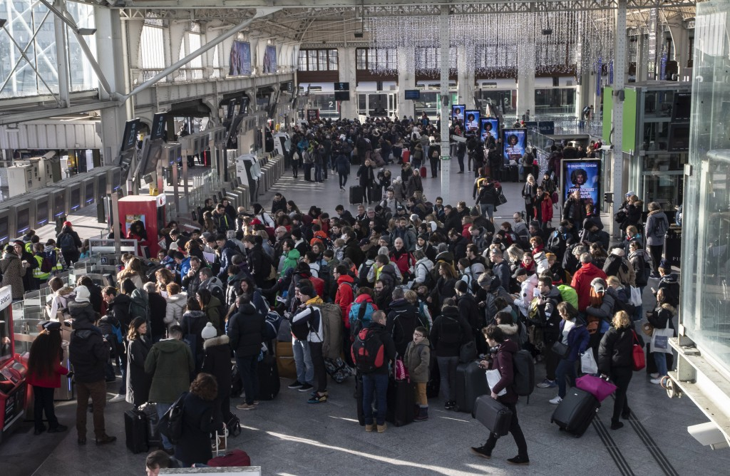 Travelers waiting to to board a train at Gare de Lyon train station in Paris, Sunday, Dec. 29, 2019. Strikes, which began Dec. 5, have disrupted trans...