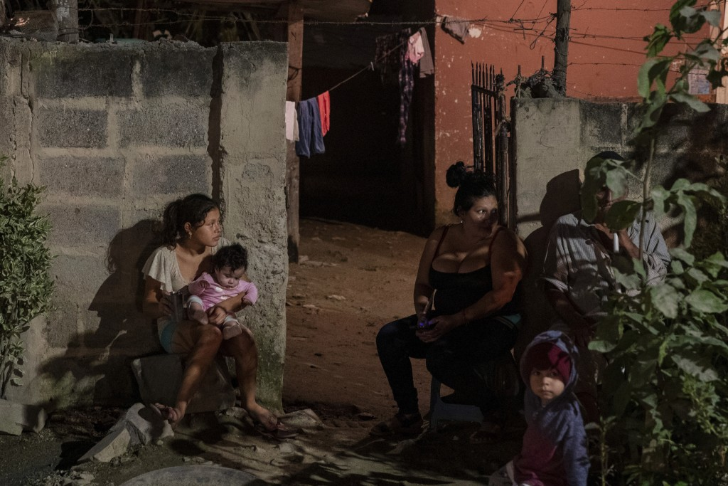 A family sits outside their home as forensic workers investigate a body at a crime scene in the Rivera Hernandez neighborhood of San Pedro Sula, Hondu...