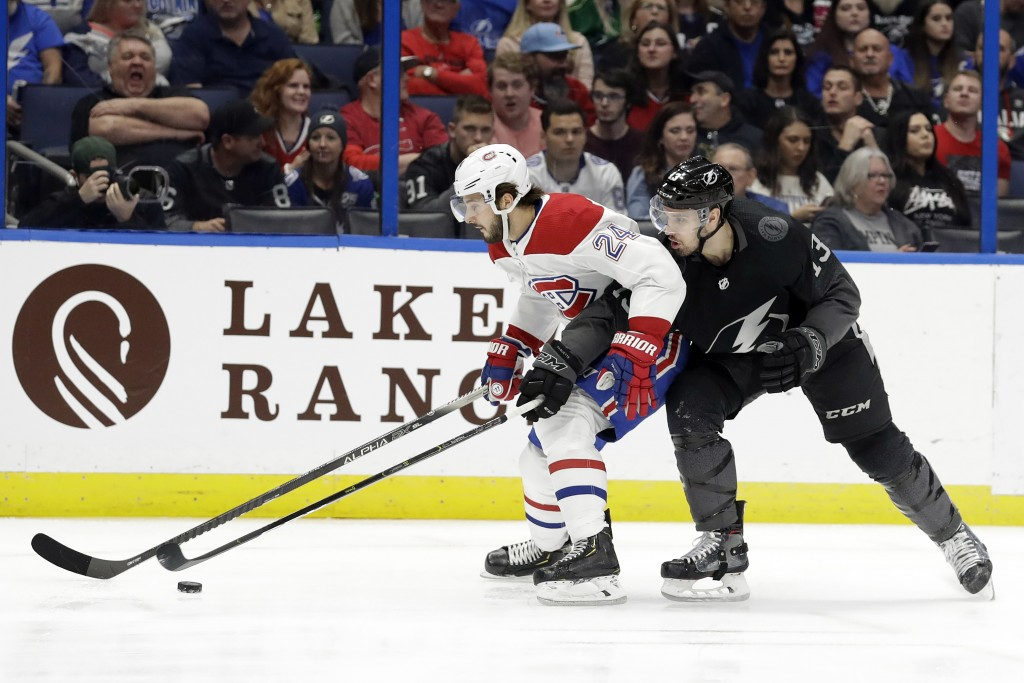 Montreal Canadiens center Phillip Danault (24) beats Tampa Bay Lightning center Cedric Paquette (13) to the puck during the first period of an NHL hoc...