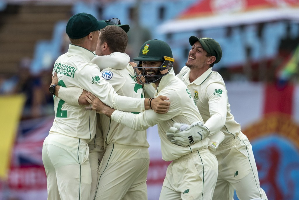 South Africa's bowler Anrich Nortje, second from left, celebrates with teammates after dismissing England's captain Joe Root on day four of the first ...