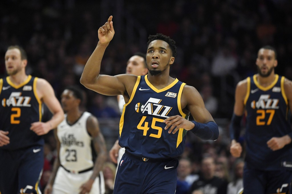 Utah Jazz guard Donovan Mitchell, center, gestures after scoring during the second half of the team's NBA basketball game against the Los Angeles Clip...