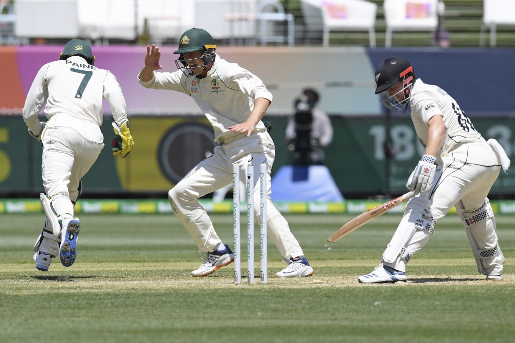 Australia's Tim Paine, left, celebrates with teammate Marnus Labuschagne, center, after stumping out New Zealand's Henry Nicholls, right, during play ...