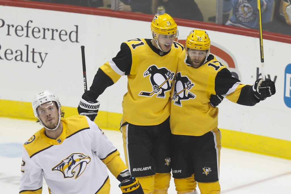 Pittsburgh Penguins' Bryan Rust (17) celebrates with Evgeni Malkin (71) after scoring against the Nashville Predators during the first period of an NH...