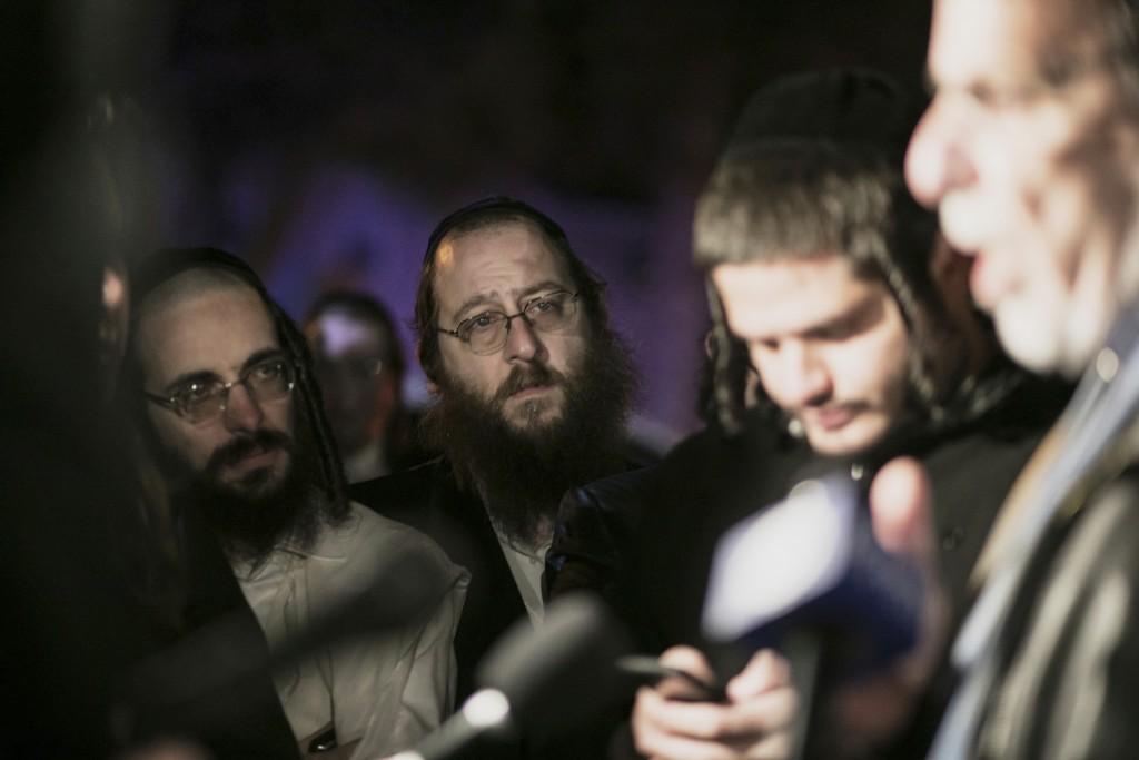 Orthodox Jewish people listen to N.Y. state Assemblyman Dov Hikind speak in Monsey, N.Y., Sunday, Dec. 29, 2019, following a stabbing late Saturday du...