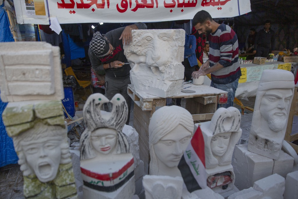 In this Tuesday, Dec. 17, 2019, photo, young Iraqi trainees work on sculptures in preparation for their upcoming art exhibition during the ongoing pro...