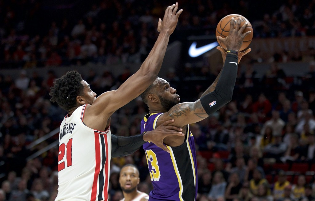 Los Angeles Lakers forward LeBron James, right, shoots in front of Portland Trail Blazers center Hassan Whiteside during the first half of an NBA bask...