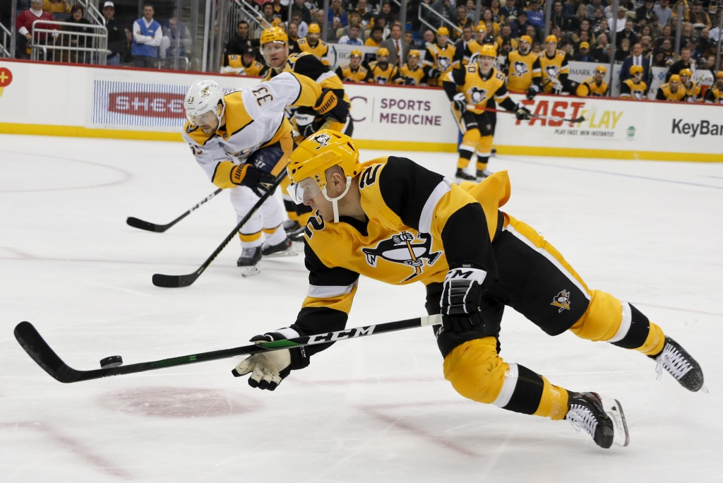 Pittsburgh Penguins' Chad Ruhwedel (2) dives to control the puck in front of Nashville Predators' Viktor Arvidsson (33) during the second period of an...