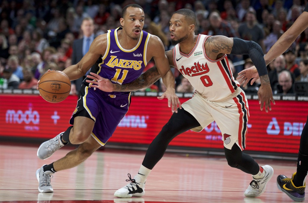 Los Angeles Lakers guard Avery Bradley, left, dribbles past Portland Trail Blazers guard Damian Lillard during the first half of an NBA basketball gam...
