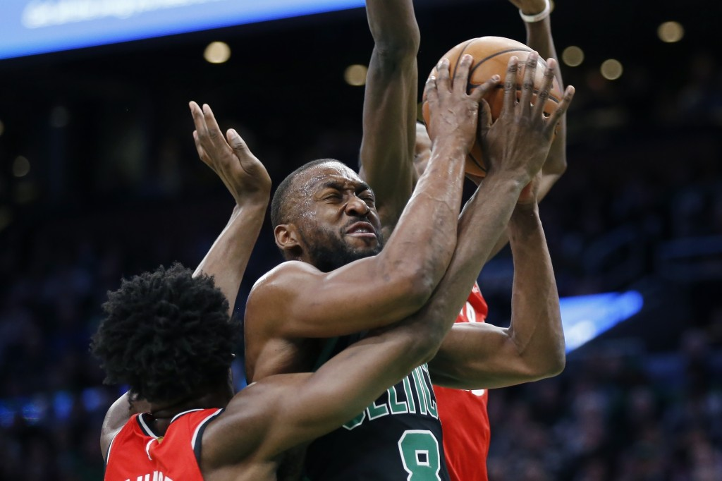 Toronto Raptors' OG Anunoby, left, and Chris Boucher, behind, double-team Boston Celtics' Kemba Walker (8) during the first half on an NBA basketball ...