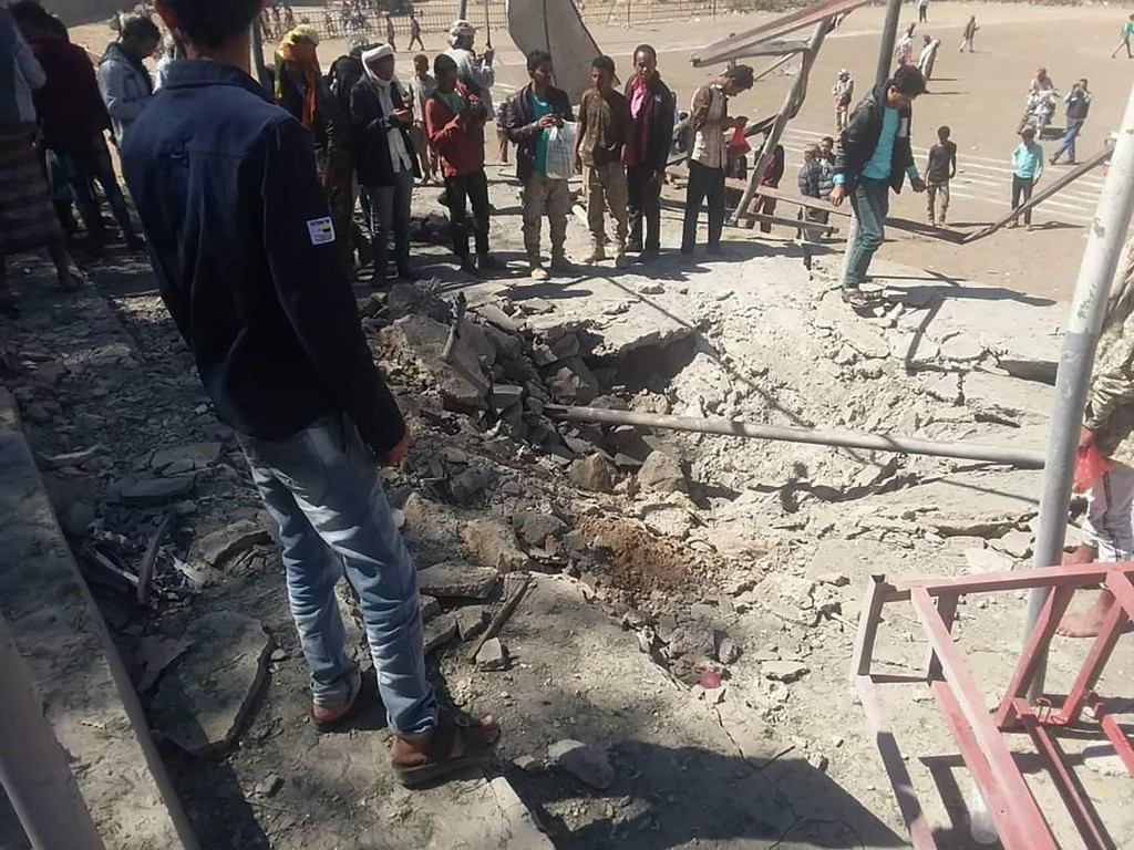 In this photo provided by southern separatist forces in Yemen, known as Resistance Force, a crowd of people stand around a crater created by a missile...