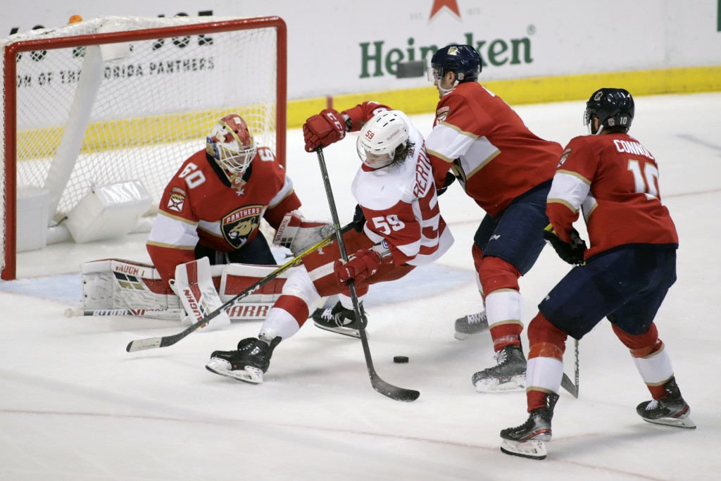 Detroit Red Wings' Tyler Bertuzzi (59) moves the puck as Florida Panthers goalkeeper Chris Driedger (60), Josh Brown, third from left, and Brett Conno...