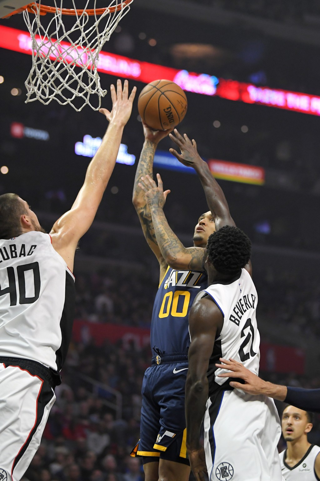 Utah Jazz guard Jordan Clarkson (00) shoots as Los Angeles Clippers center Ivica Zubac, left, and guard Patrick Beverley defend during the first half ...
