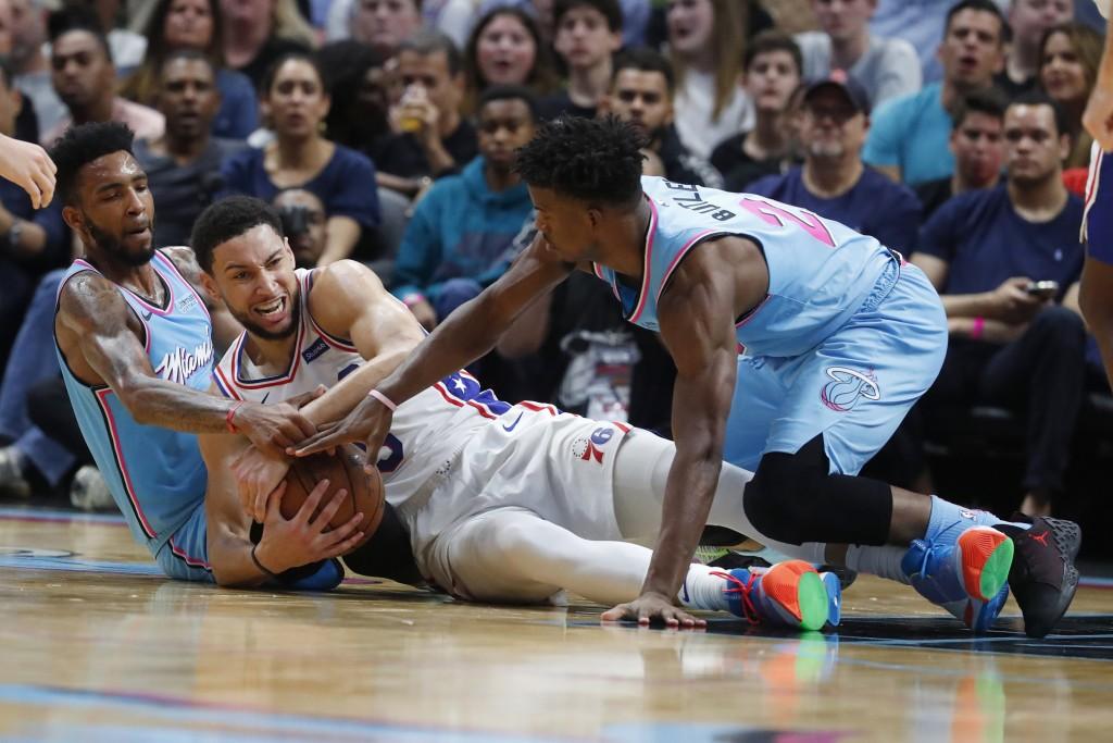 Philadelphia 76ers guard Ben Simmons, center, Miami Heat forwards Derrick Jones Jr., left, and Jimmy Butler, right, battle for the ball during the fir...