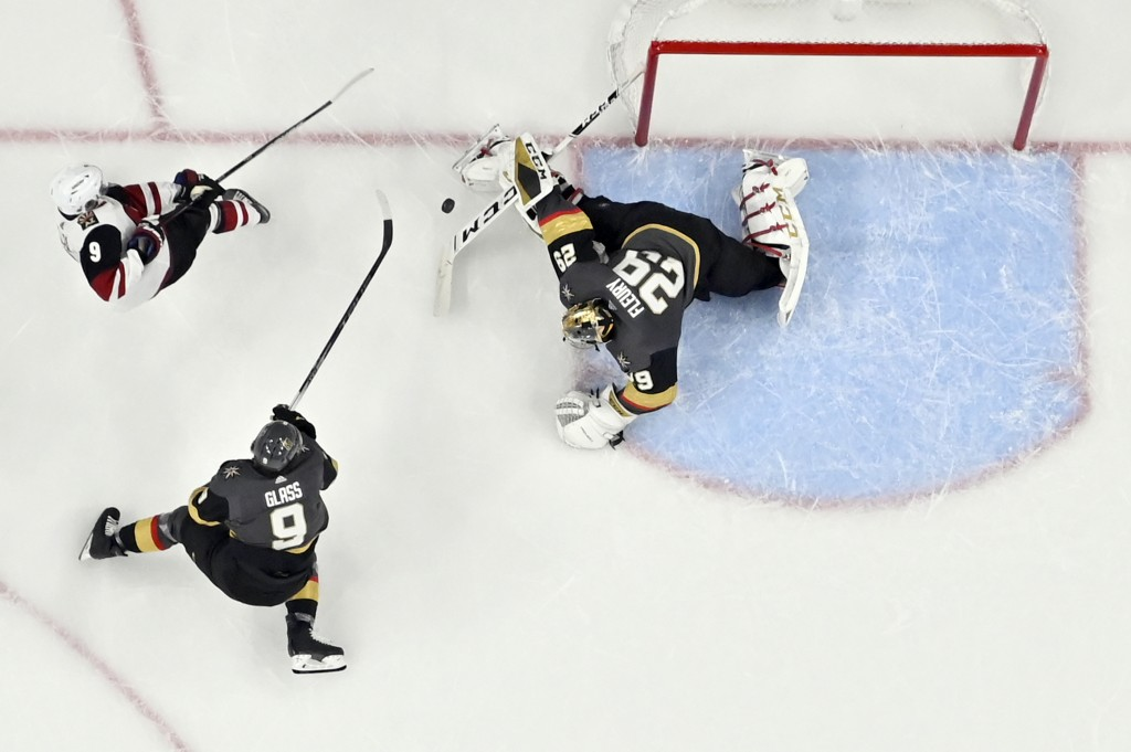 Arizona Coyotes center Clayton Keller, top left, shoots against Vegas Golden Knights goaltender Marc-Andre Fleury (29) and center Cody Glass during th...