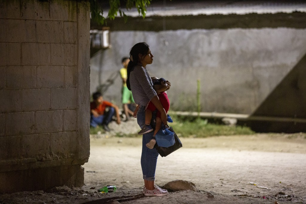A woman holds a child near a crime scene as forensic workers inspect a body on the street in the Rivera Hernandez neighborhood of San Pedro Sula, Hond...