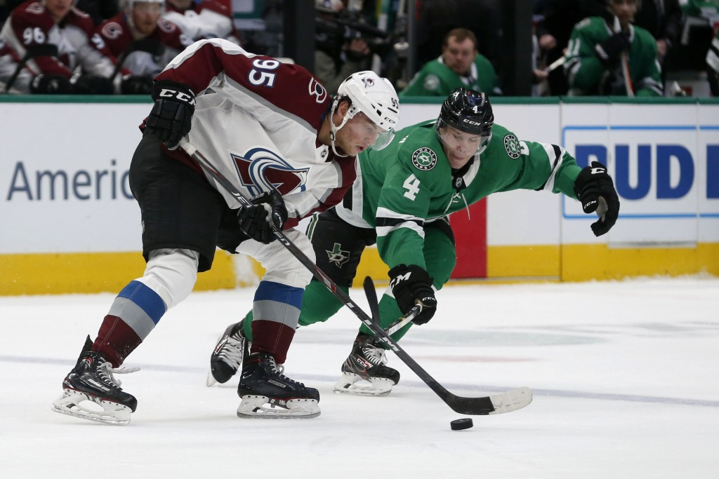 Colorado Avalanche left wing Andre Burakovsky (95) tries to get the puck past Dallas Stars defenseman Miro Heiskanen (4) during the first period of an...