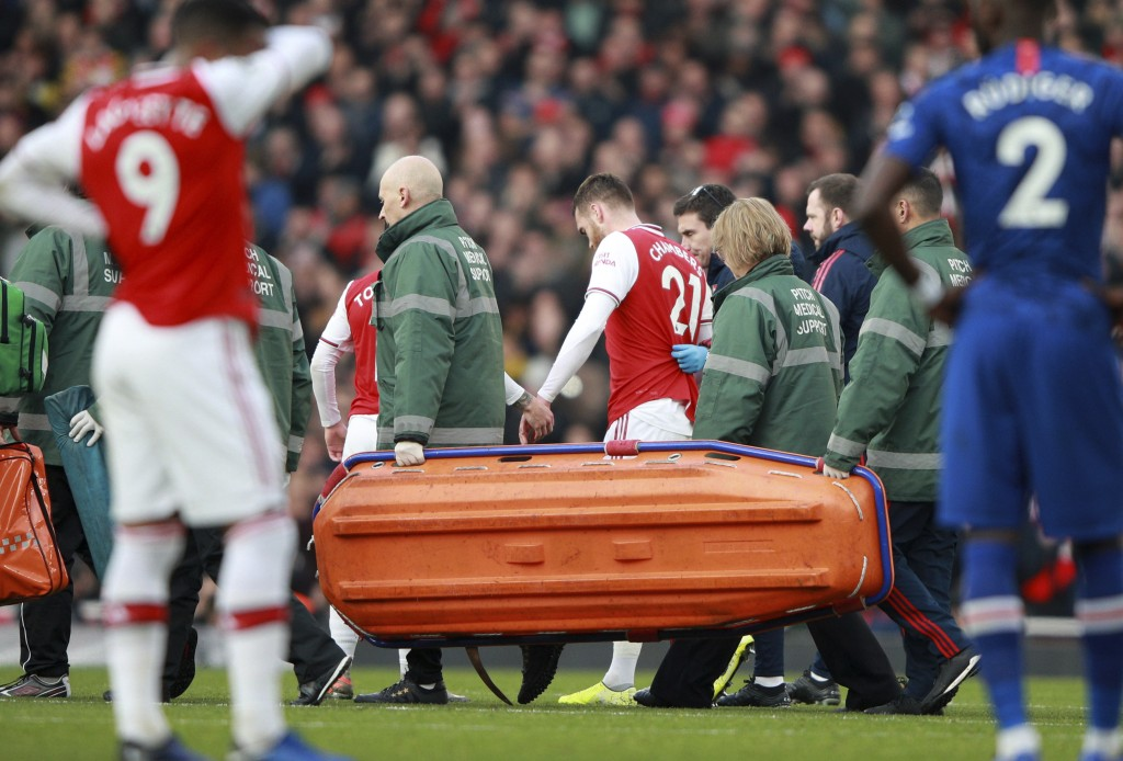 Arsenal's Calum Chambers leaves the pitch after being injured during the English Premier League soccer match between Arsenal and Chelsea, at the Emira...