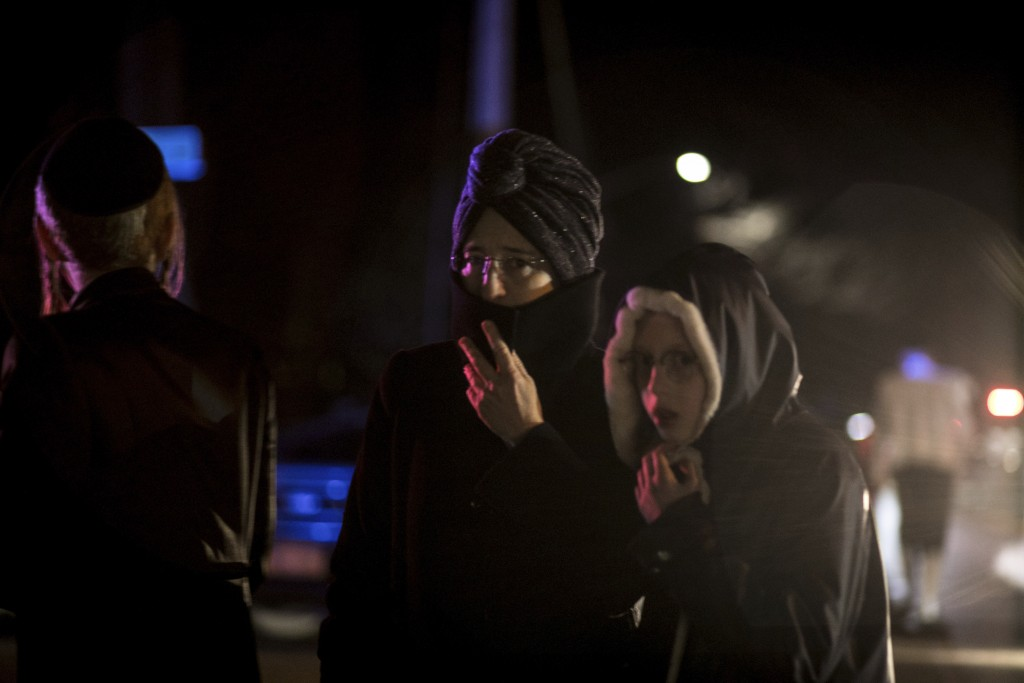 Onlookers including Orthodox Jewish stand on the corner of Forshay Road in Monsey, N.Y., Sunday, Dec. 29, 2019, down the street from the scene of a st...